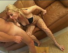 Fishnet clad blonde gives a guy a sexy footjob